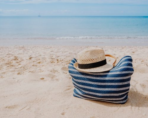 Blue beach bag with hat on the sandy beach with the blue sky background summer holiday