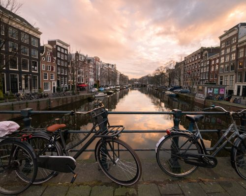 Amsterdam, Netherlands – March 11, 2018: Bicycles locked to the bar of a bridge over a canal lined by traditional architecture houses at sunset in the city center of Amsterdam, the Netherlands.